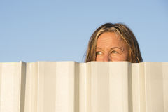 Aufpassende Augen der Frau hinter dem Zaun im Freien Stockbild
