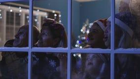 Aufpassende Feuerwerke der glücklichen Familie durch Fenster lizenzfreies stockfoto