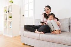 Aufpassende Filme der Mutter und der Tochter mit Haupt-Fernsehen stockbild