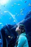 Aufpassende Fische der jungen hübschen Frau in einem tropischen Aquarium Lizenzfreie Stockbilder