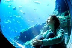 Aufpassende Fische der jungen hübschen Frau in einem tropischen Aquarium Stockfotos