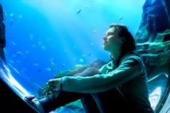Aufpassende Fische der jungen hübschen Frau in einem tropischen Aquarium Lizenzfreie Stockfotos