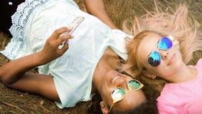 Aufpassende Fotos des hübschen Mischrassemädchens auf Smartphone, ihr Freund, der hinten liegt lizenzfreies stockbild