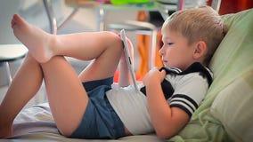Aufpassende Geschichten des kleinen Jungen auf Tablette auf Bett stock footage