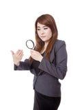 Aufpassende Hand der asiatischen unglücklichen Gebrauchs-Lupe der Geschäftsfrau Stockfotografie