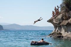 Aufpassende Kerle des Mädchens springen in das Meer von den Felsen Stockbild