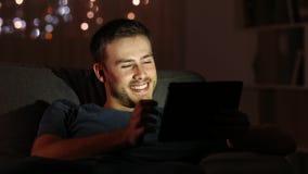 Aufpassende Medien des Mannes mit einer Tablette in der Nacht zu Hause stock video footage