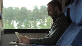 Aufpassende Nachrichten des ernsten Mannes auf einer Tablette in einem Zug stock video footage