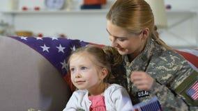 Aufpassende Parade des glücklichen weiblichen Soldaten und der netten Tochterstaatsflagge zusammen stock video