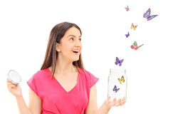 Aufpassende Schmetterlinge des glücklichen Mädchens, die einem offenen Glas entgehen Stockfotografie