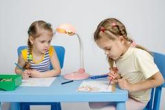 Aufpassende Schwester des Mädchens zeichnet Farben Lizenzfreies Stockfoto