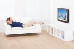 Aufpassende Strandansicht des Mannes im Fernsehen zu Hause Lizenzfreie Stockfotos
