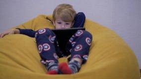 Aufpassende Tablette des Jungen beim Sitzen auf einem Puff stock video
