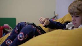Aufpassende Tablette des Jungen beim Sitzen auf einem Puff stock video footage