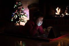 Aufpassende Tablette des Jungen neben Weihnachtsbaum a Lizenzfreies Stockfoto