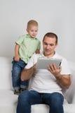 Aufpassende Tablette des Vatis und des Sohns lizenzfreies stockfoto