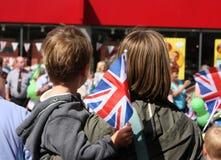 Aufpassende und wellenartig bewegende Union- Jackflaggen des Jungen und der Mama Lizenzfreies Stockbild