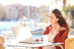 Aufpassende Videos der Frau in einem Laptop draußen Lizenzfreie Stockbilder