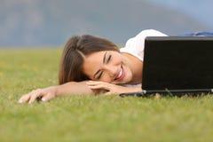 Aufpassende Videos der glücklichen Frau in einem Laptop, der auf dem Gras liegt Stockfotos