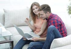Aufpassende Videos der jungen Paare auf Laptop Lizenzfreie Stockfotografie