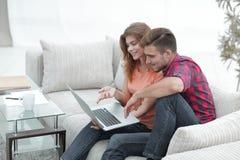 Aufpassende Videos der jungen Paare auf Laptop Stockfotografie