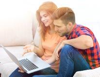 Aufpassende Videos der jungen Paare auf Laptop Stockbild