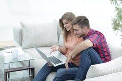 Aufpassende Videos der jungen Paare auf Laptop Stockbilder