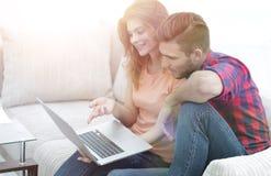 Aufpassende Videos der jungen Paare auf Laptop Stockfoto