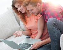 Aufpassende Videos der jungen Paare auf Laptop Lizenzfreie Stockbilder