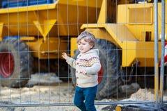 Aufpassender Bagger des kleinen Jungen auf Bauzone, draußen Stockfotografie
