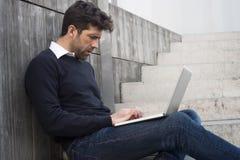 Aufpassender Computer des jungen Mannes Stockfotos