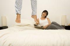 Aufpassender Ehemann der Frau springen auf Bett lizenzfreie stockbilder