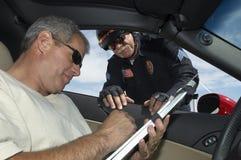 Aufpassender Fahrer des Polizeibeamten Papiere unterzeichnen Stockfoto