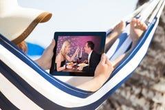Aufpassender Film der Frau auf digitaler Tablette in der Hängematte Lizenzfreie Stockbilder