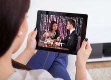 Aufpassender Film der jungen Frau an der Tablette Lizenzfreies Stockbild