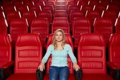 Aufpassender Film der jungen Frau im Theater Lizenzfreie Stockfotografie