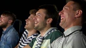 Aufpassender Film der jungen Leute im Kino essen stock video