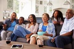Aufpassender Film der multi Generationsschwarz-Familie im Fernsehen zusammen stockbild