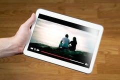 Aufpassender Film des Mannes online mit tragbarem Gerät stockfotografie