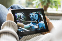 Aufpassender Filmavatara des Mannes auf iPad Lizenzfreies Stockbild