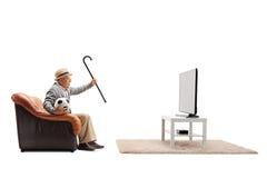 Aufpassender Fußball des älteren Mannes im Fernsehen und Zujubeln stockfoto