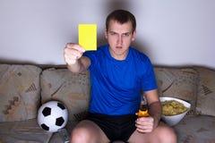 Aufpassender Fußball des jungen Mannes auf Fernsehen und dem Zeigen der gelben Karte Stockfotografie