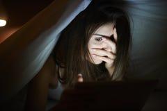 Aufpassender Horrorfilm der Frau auf Tablette Stockfoto