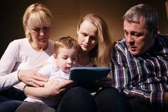 Aufpassender Junge der Familie, der Spiel auf Berührungsfläche spielt stockfoto