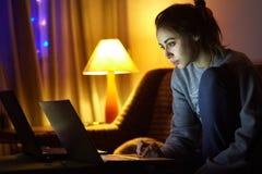 Aufpassender Laptop der Frau Lizenzfreie Stockbilder