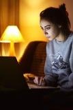 Aufpassender Laptop der Frau Lizenzfreie Stockfotos