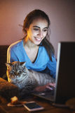 Aufpassender Laptop der Frau mit Katze auf den Händen Lizenzfreies Stockbild