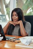 Aufpassender Laptop der schönen schwarzen Geschäftsfrau lizenzfreies stockbild