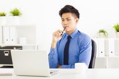 aufpassender Laptop und Planung des Geschäftsmannes lizenzfreie stockbilder