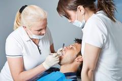 Aufpassender praktizierender Zahnarzt des Zahnarzthelfers Stockfotografie